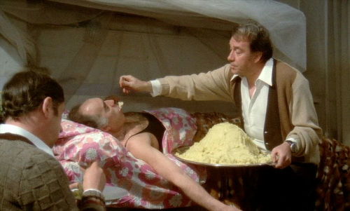 """Σκηνή από την ιστορική ταινία του Μάρκο Φερέρι """"Το Μεγάλο Φαγοπότι"""". Ο Ούγκο Τονιάτσι ταΐζει τον ήδη σκασμένο από το φαγητό Μισέλ Πικολί. Την πλάτη στον φακό έχει γυρισμένη ο Φιλίπ Νουαρέ."""