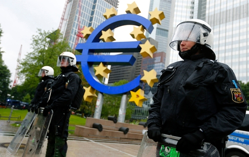 Riot police stand near the euro sign in front of the European Central Bank (ECB) headquarters during an anti-capitalist